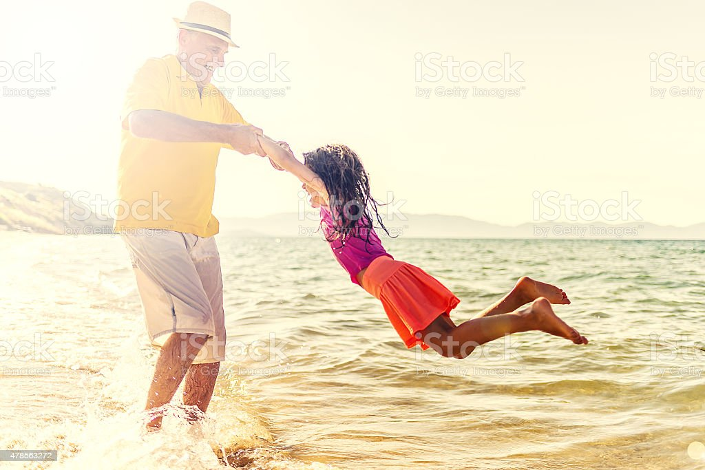 Grandfather And Granddaughter at the beach stock photo