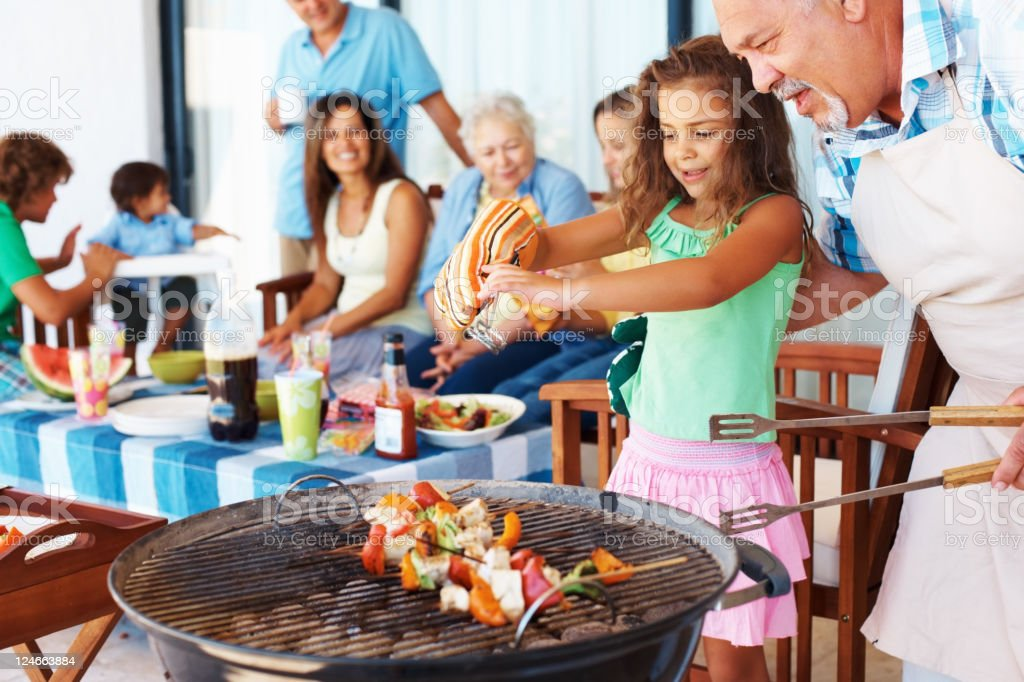 Grandfather and granddaughter barbecuing with family royalty-free stock photo