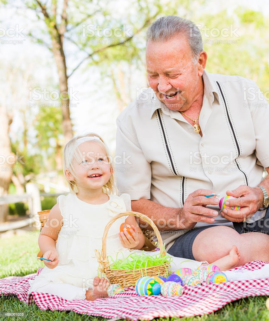 Grandfather and Granddaughter Coloring Easter Eggs on Blanket At stock photo