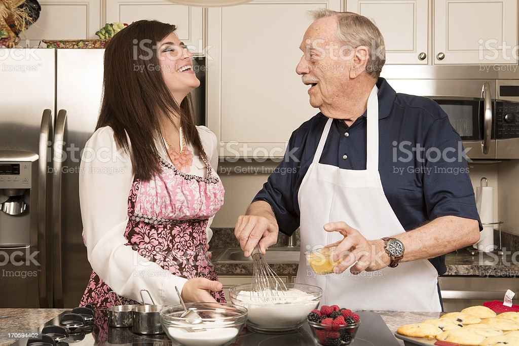 Grandfather and Granddaughter cooking in kitchen royalty-free stock photo