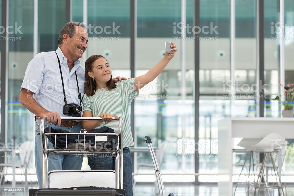 Grandfather and granddaughter making a selfie before boarding stock photo