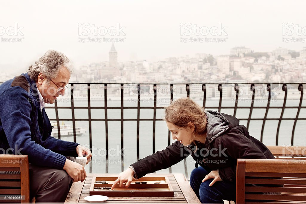 Grandfather and granddaughter playing backgammon stock photo