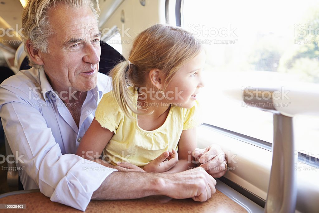 Grandfather And Granddaughter Relaxing On Train Journey stock photo