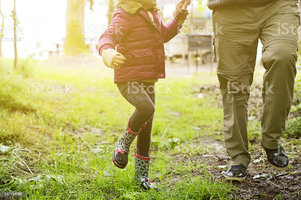 Grandfather and granddaughter running outdoor. stock photo