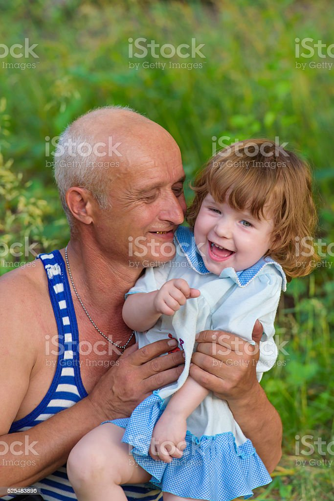 Grandfather and granddaughter smiling at prerode stock photo