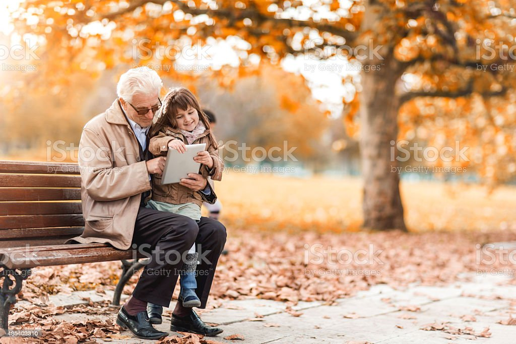 Grandfather and granddaughter using digital tablet in autumn. stock photo