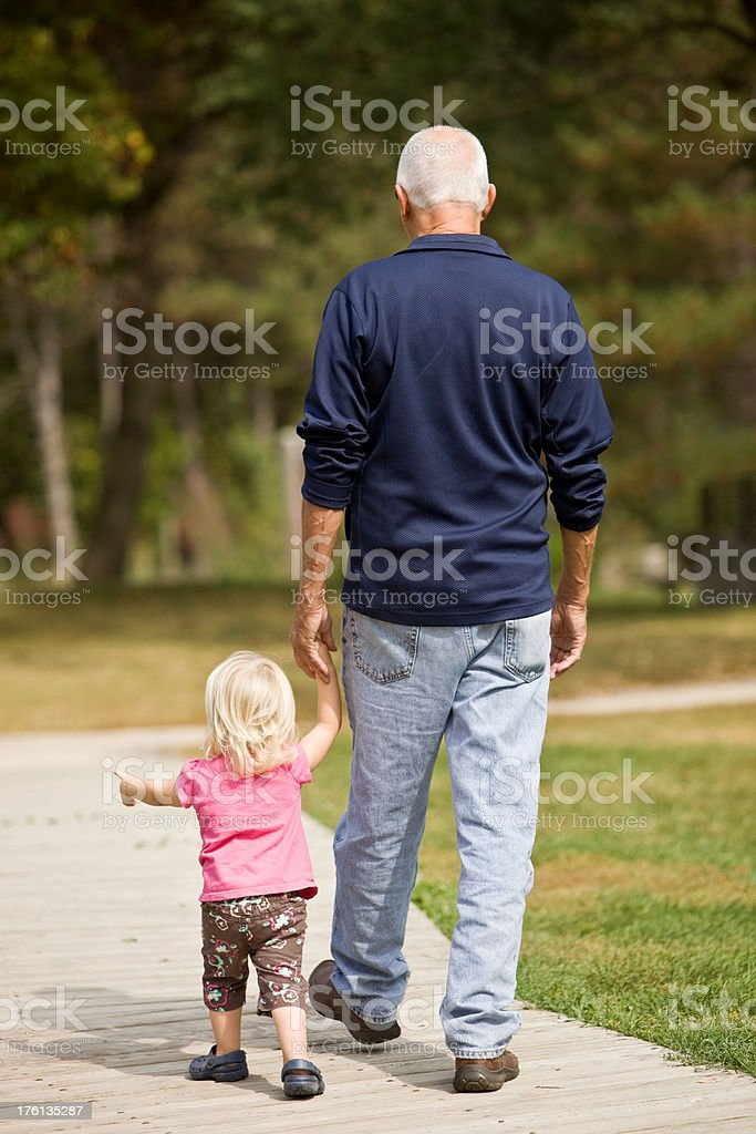 Grandfather and Granddaughter walking holding hands royalty-free stock photo