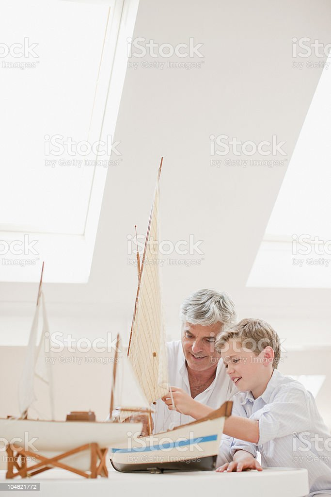Grandfather and grandson assembling model sailboat stock photo