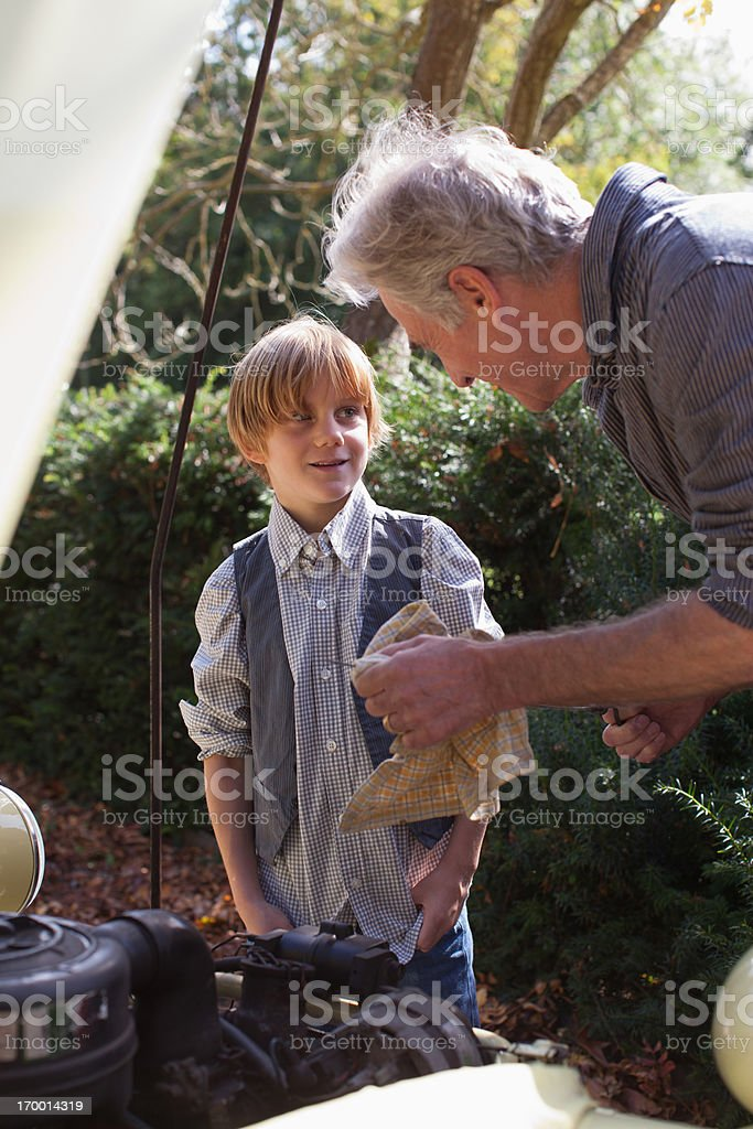 Grandfather and grandson catching fish with fishing rod stock photo