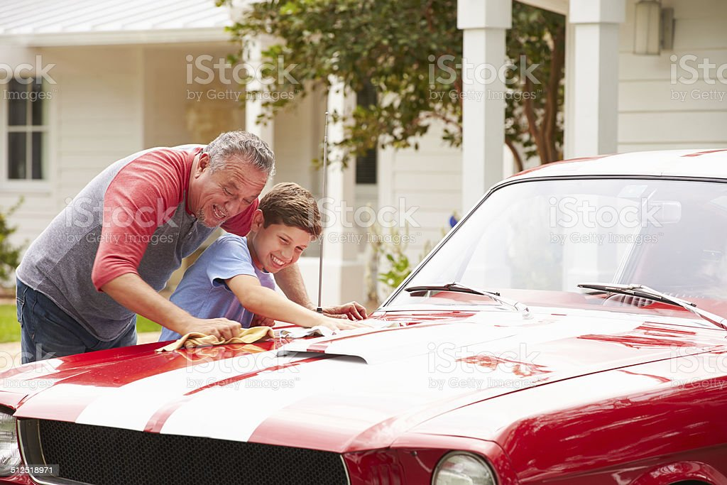 Grandfather And Grandson Cleaning Restored Classic Car stock photo