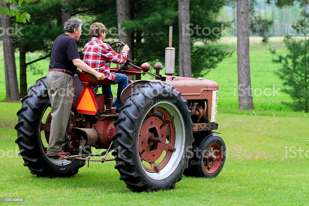 Grandfather and Grandson Driving a Vintage Tractor royalty-free stock photo