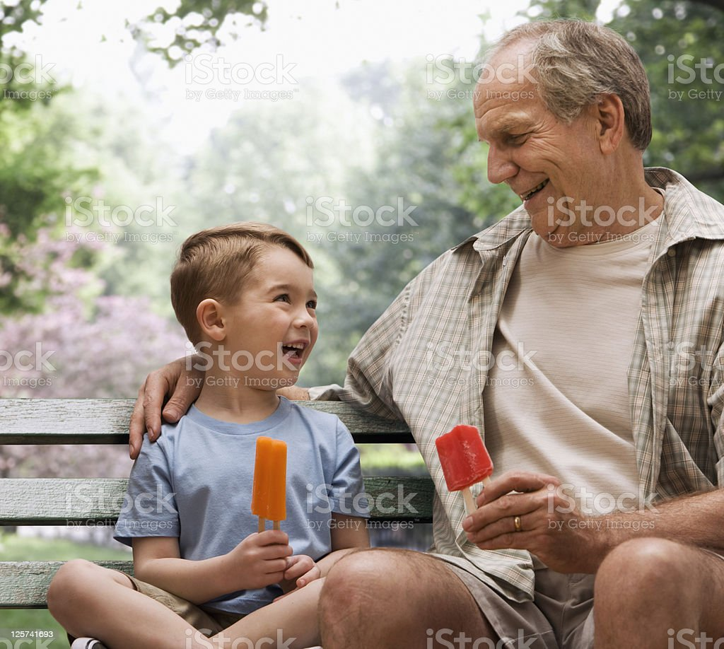 Grandfather and Grandson eating ice cream in a park royalty-free stock photo