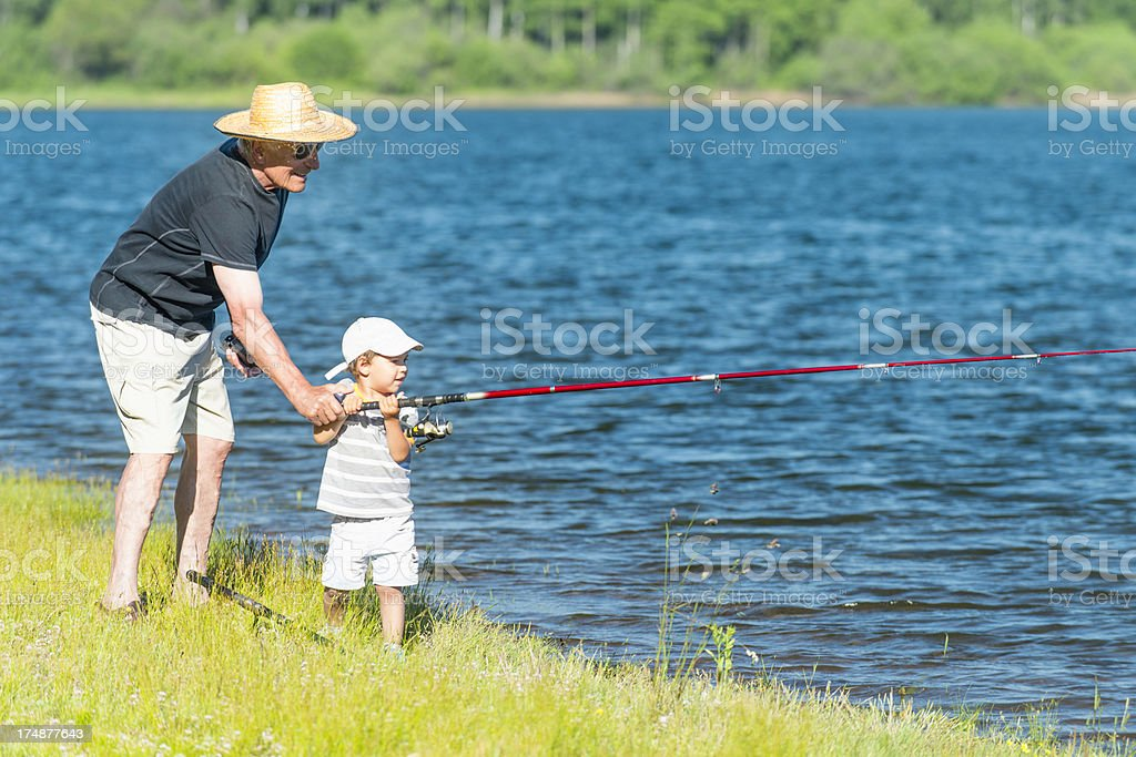 Grandfather and grandson enjoy fishing royalty-free stock photo