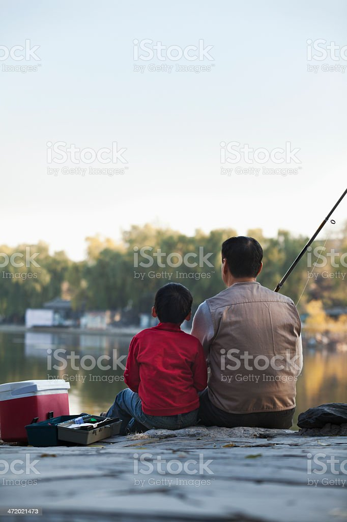 Grandfather and grandson fishing at a lake royalty-free stock photo