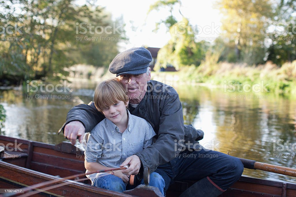 Grandfather and grandson fishing in boat royalty-free stock photo