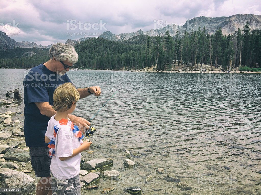 Grandfather and grandson fishing on a stormy mountain lake stock photo