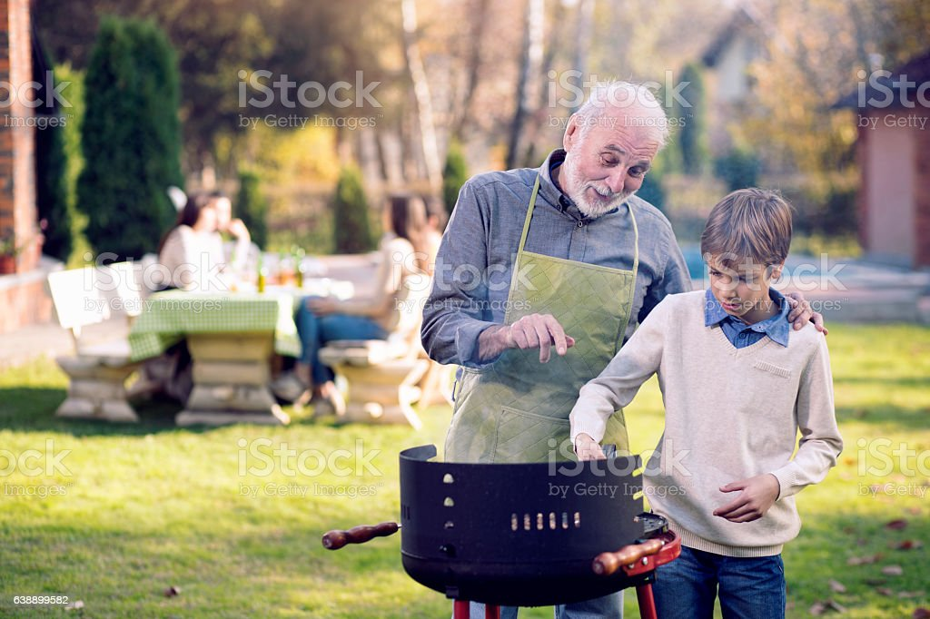 Grandfather and Grandson Having a Barbecue stock photo