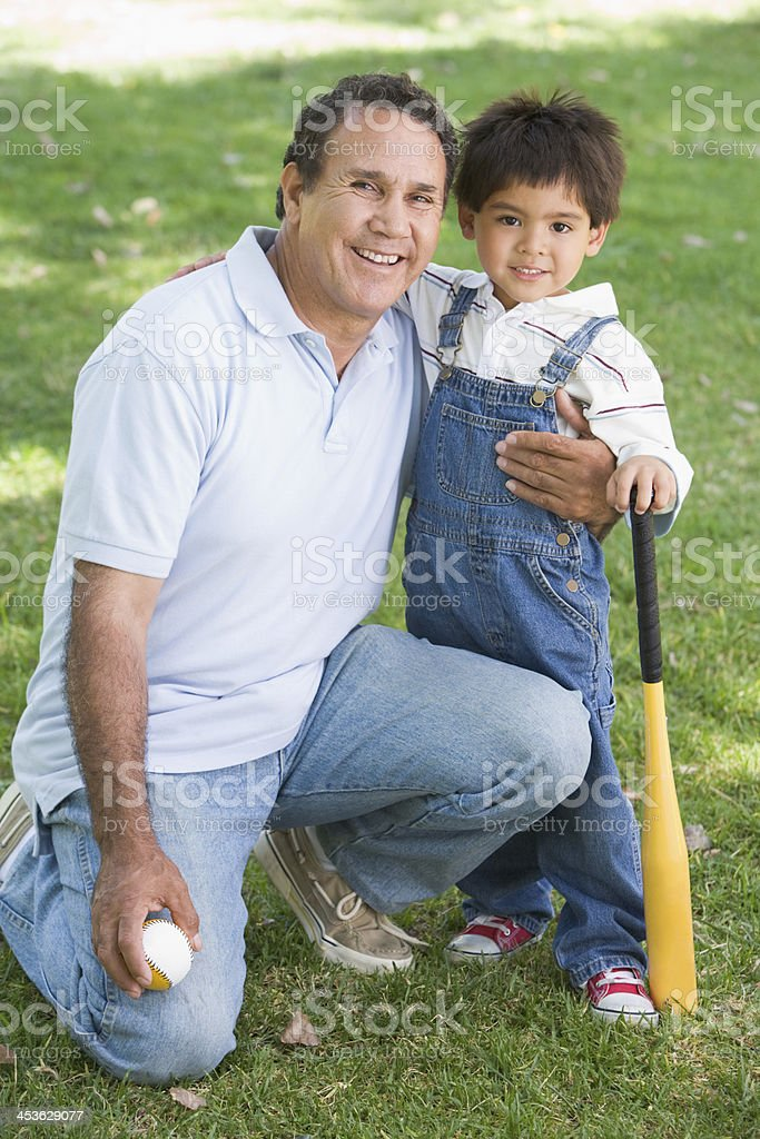 Grandfather and grandson holding baseball bat royalty-free stock photo