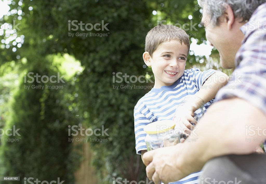 Grandfather and grandson holding insect jar royalty-free stock photo
