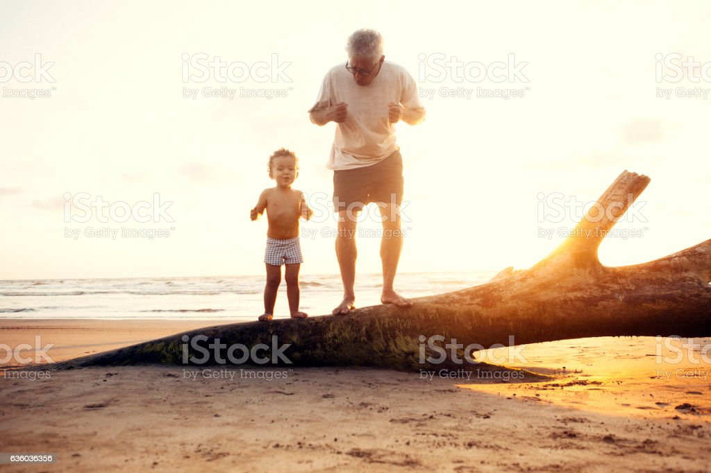 Grandfather and grandson in the beach stock photo