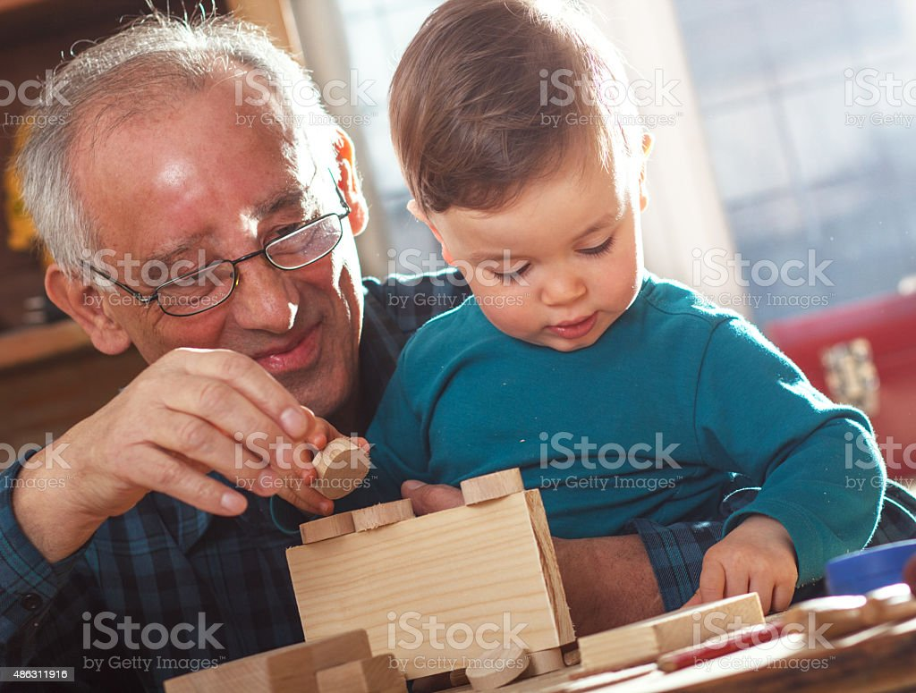 Grandfather and grandson in workshop stock photo