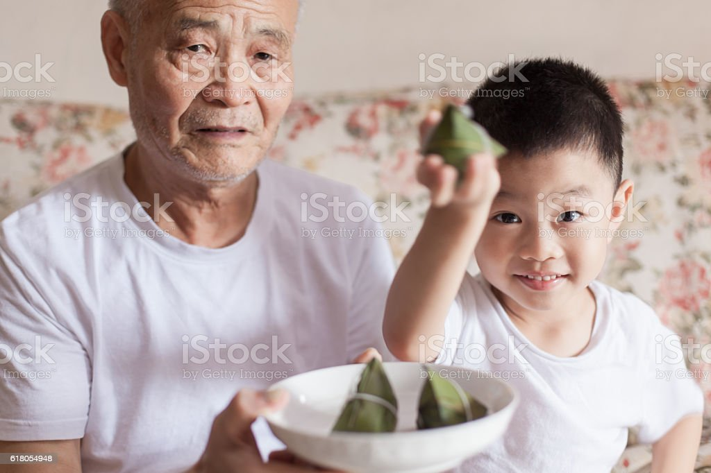 Grandfather and grandson introducing zongzi stock photo