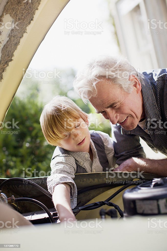 Grandfather and grandson looking under automobile hood stock photo