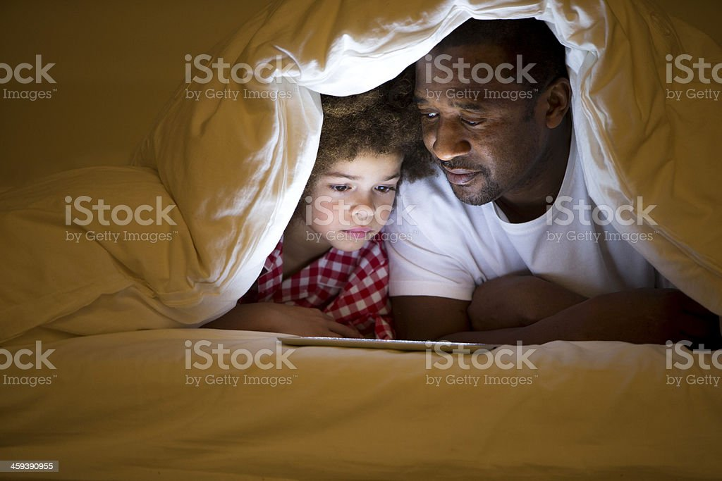 Grandfather and Grandson lying in bed royalty-free stock photo