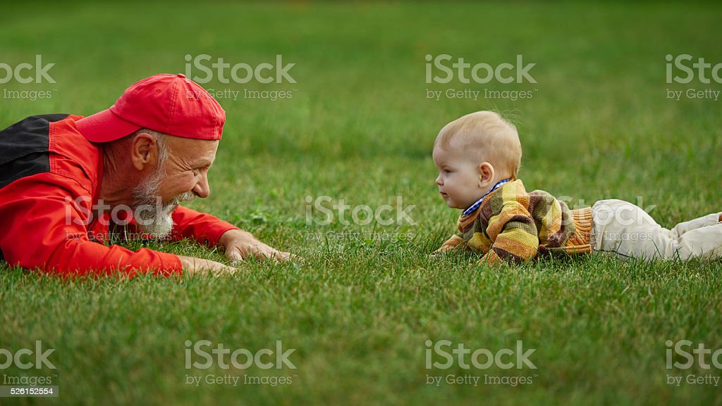 grandfather and grandson lying on grass stock photo
