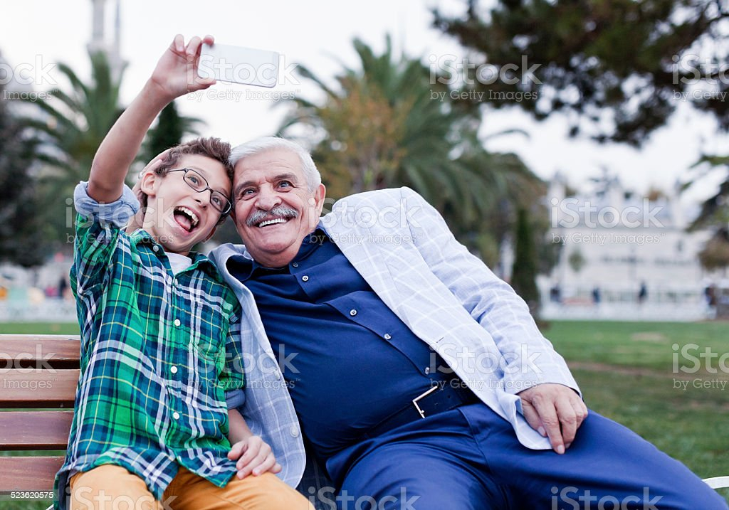 Grandfather and grandson make selfie in Istanbul. stock photo