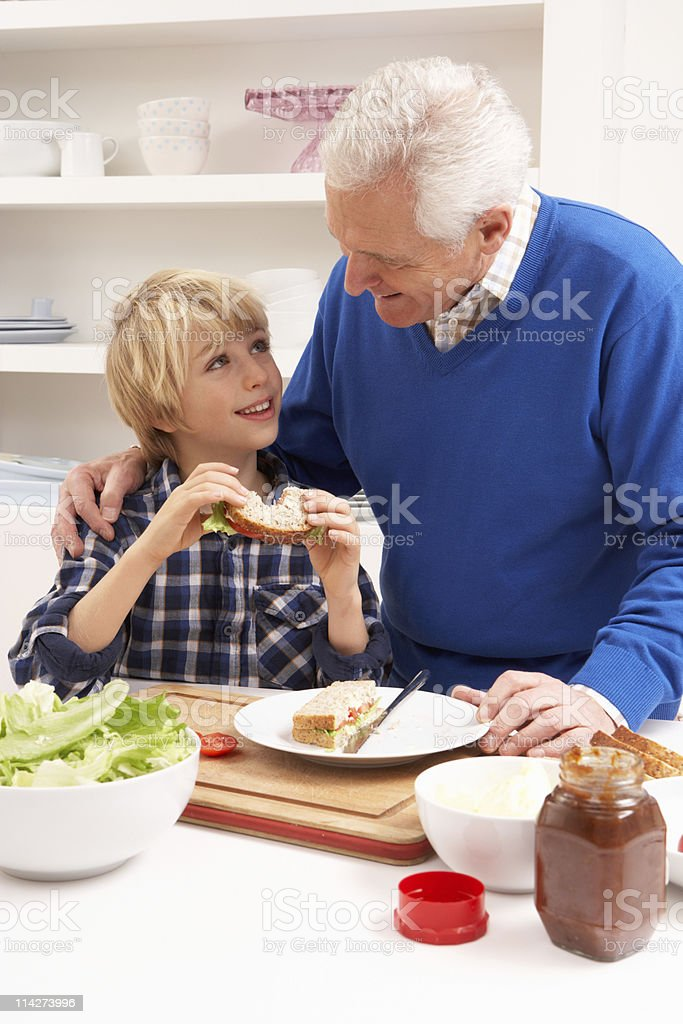 Grandfather And Grandson Making Sandwich In Kitchen royalty-free stock photo