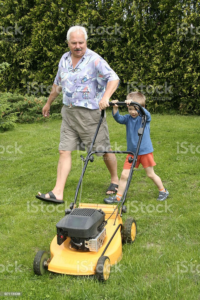 Grandfather and grandson mowing grass royalty-free stock photo