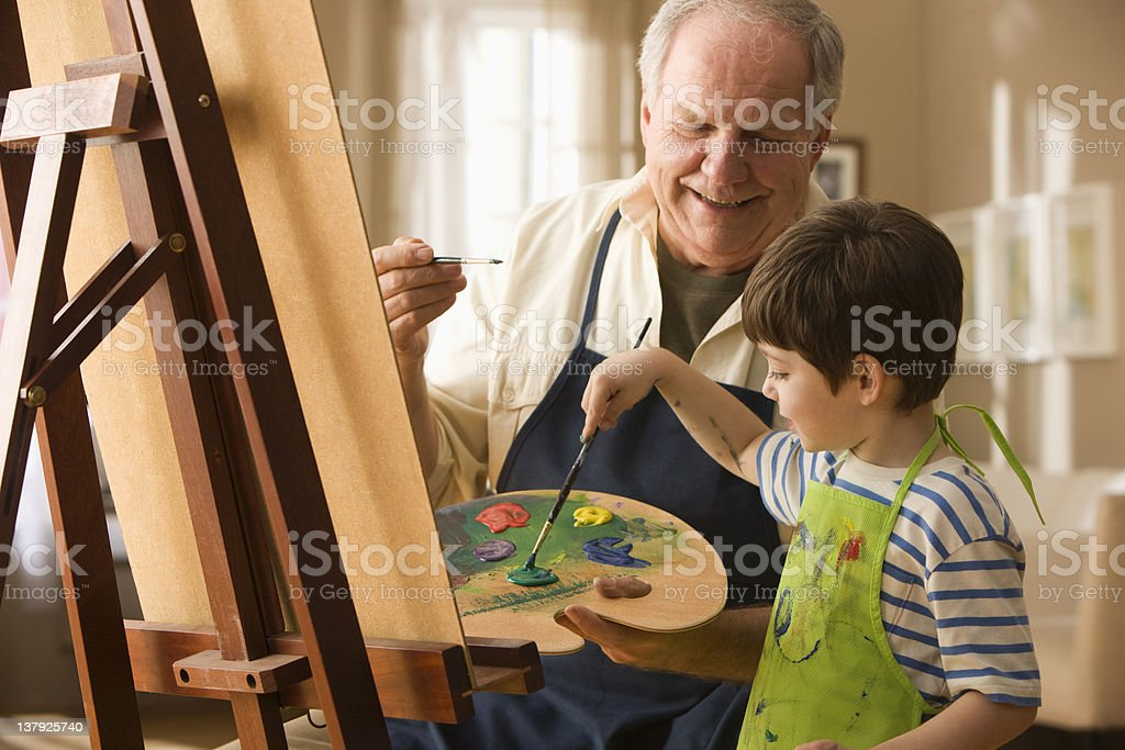 Grandfather and grandson painting on canvas royalty-free stock photo
