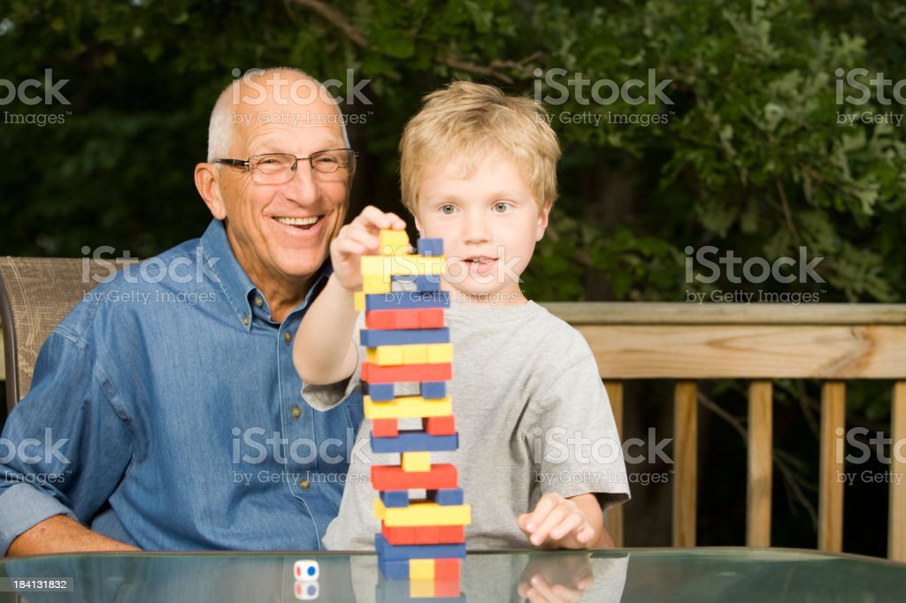 Grandfather and Grandson Play Stacking Tower Skill Game royalty-free stock photo