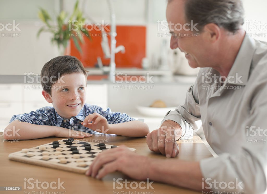Grandfather and grandson playing checkers together royalty-free stock photo