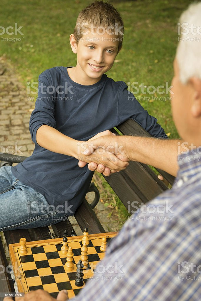 Grandfather and grandson playing chess in the park stock photo