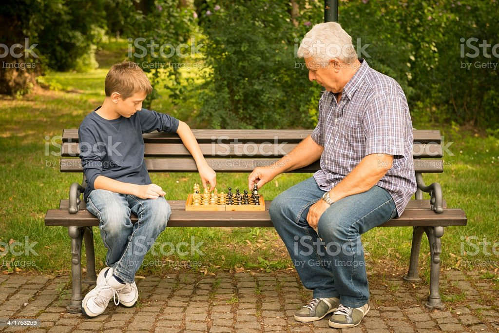 Grandfather and grandson playing chess in the park royalty-free stock photo