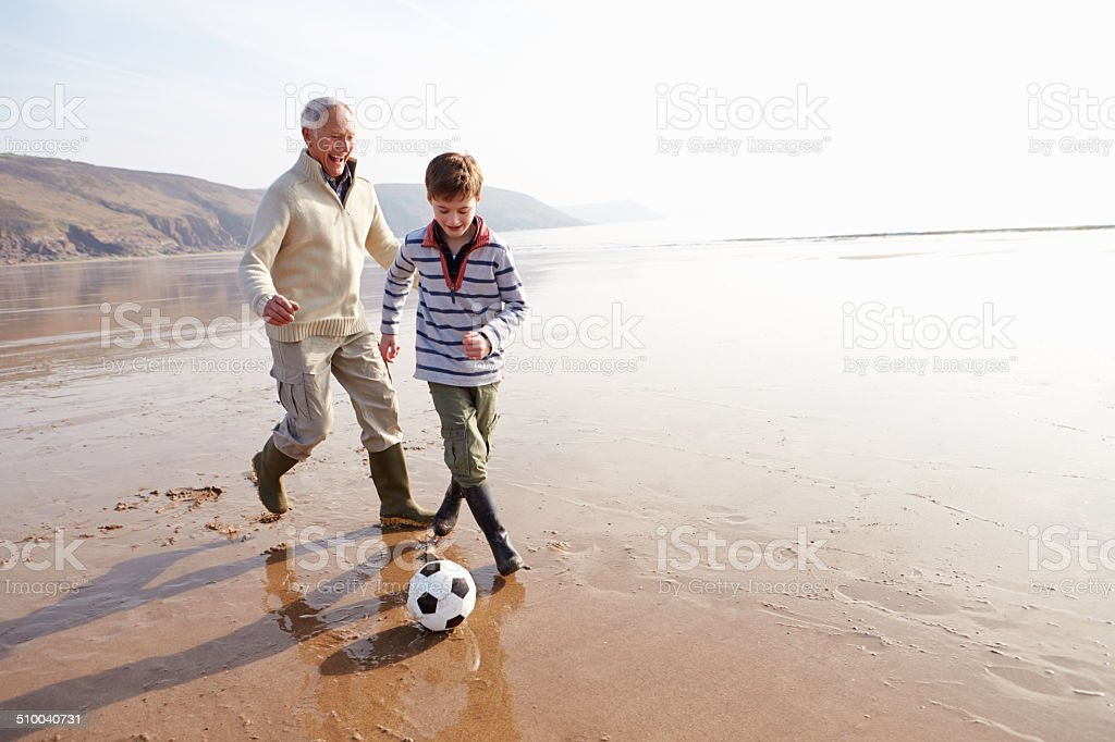 Grandfather And Grandson Playing Football On Winter Beach stock photo