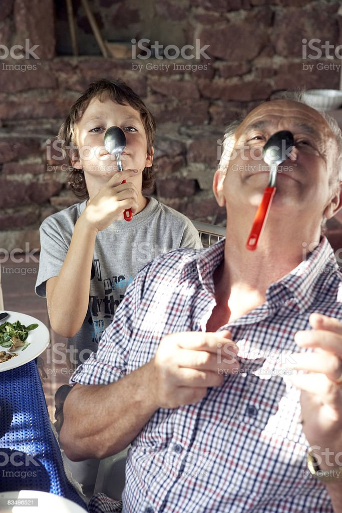grandfather and grandson playing with spoons stock photo