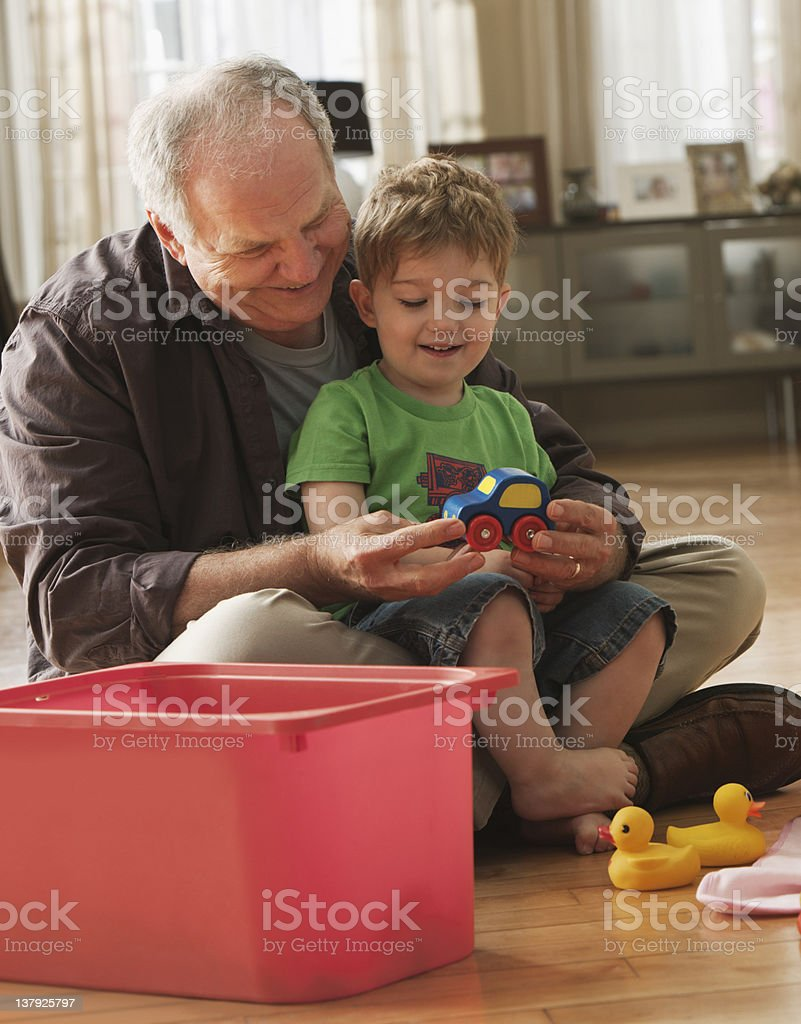 Grandfather and grandson playing with toys stock photo
