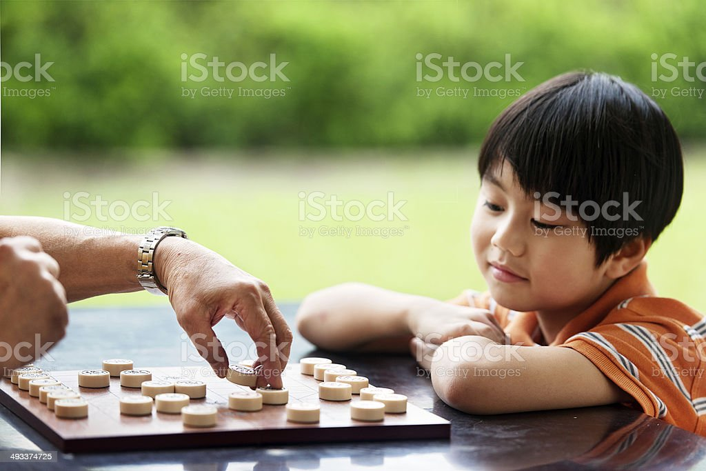 Grandfather and grandson playing Xiangqi (chinese chess) stock photo