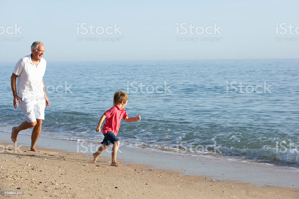 Grandfather And Grandson Running Along Beach royalty-free stock photo