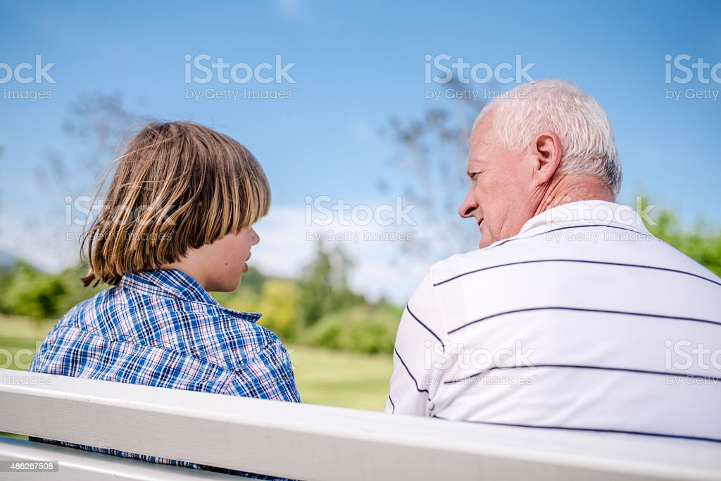 Grandfather and grandson sitting at park stock photo
