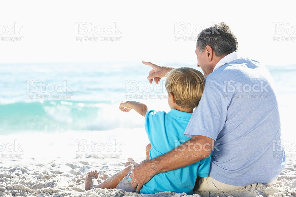 Grandfather And Grandson Sitting On Beach stock photo