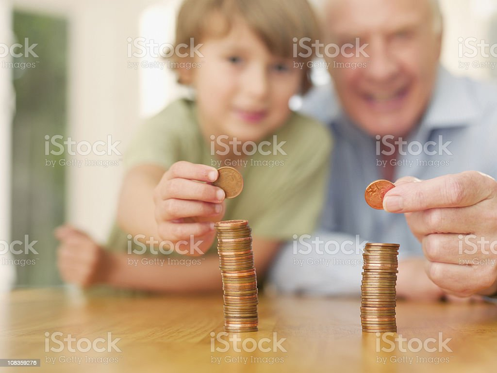 Grandfather and grandson stacking coins royalty-free stock photo