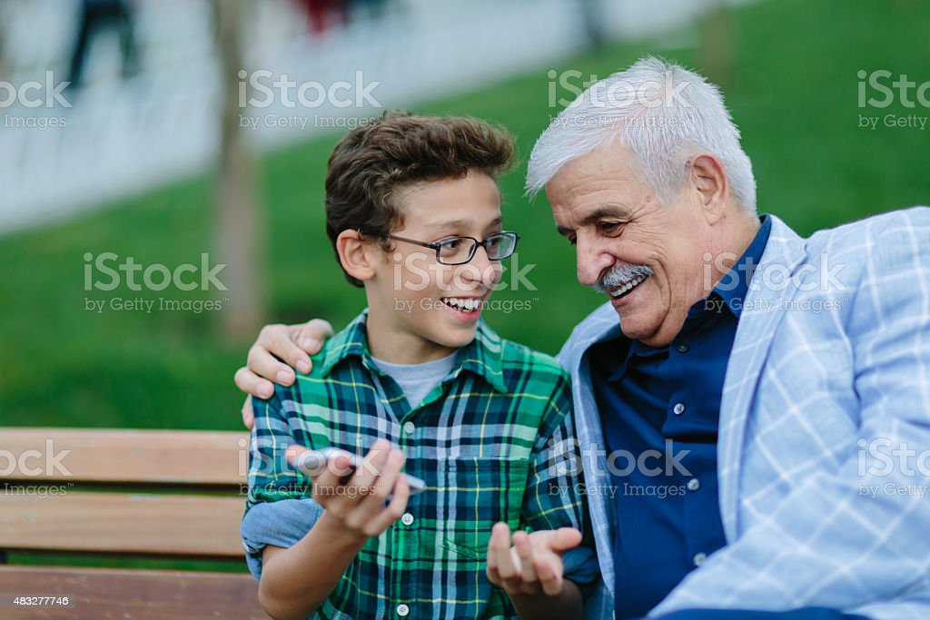 Grandfather and grandson talking in the park stock photo