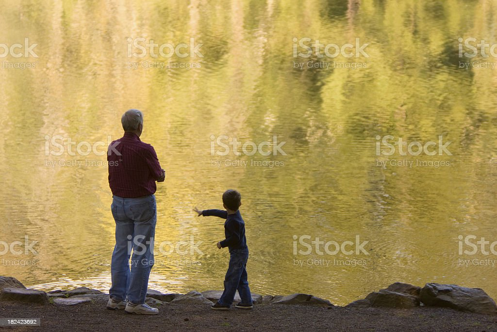 Grandfather and Grandson throwing Rocks in Lake stock photo