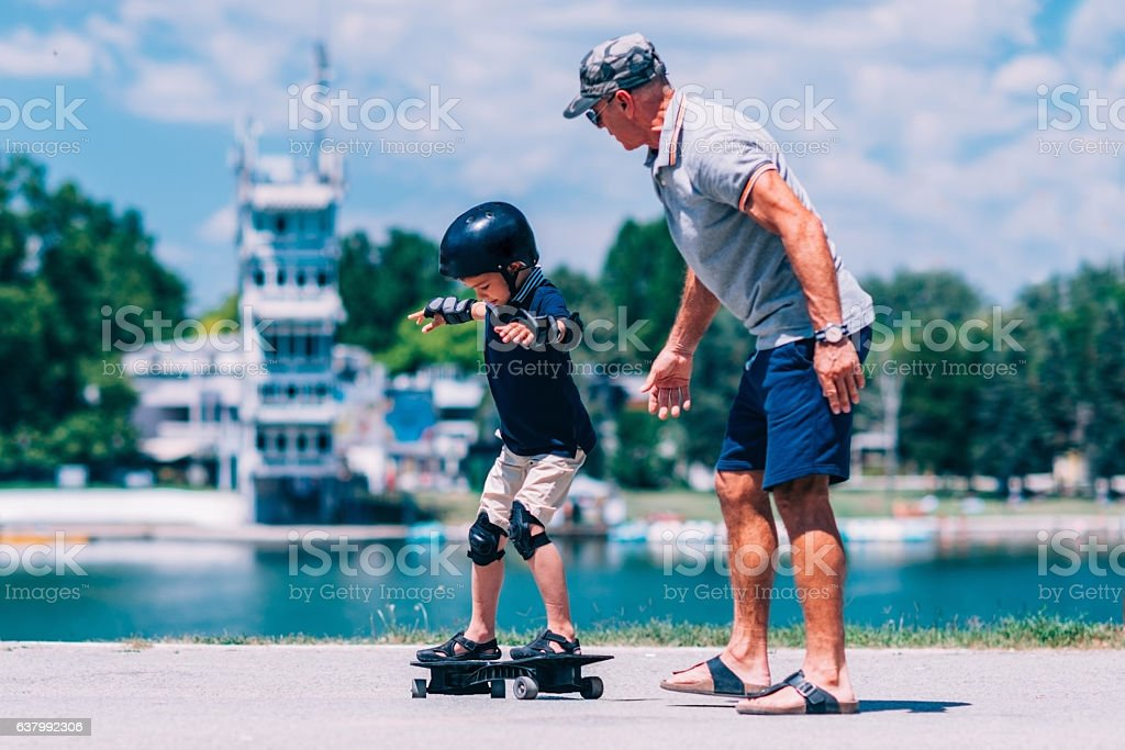 Grandfather and grandson trying a snakeboard stock photo