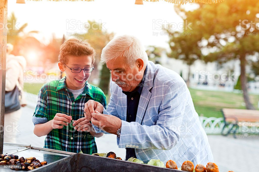 Grandfather and grandson trying chestnuts in Istanbul. stock photo