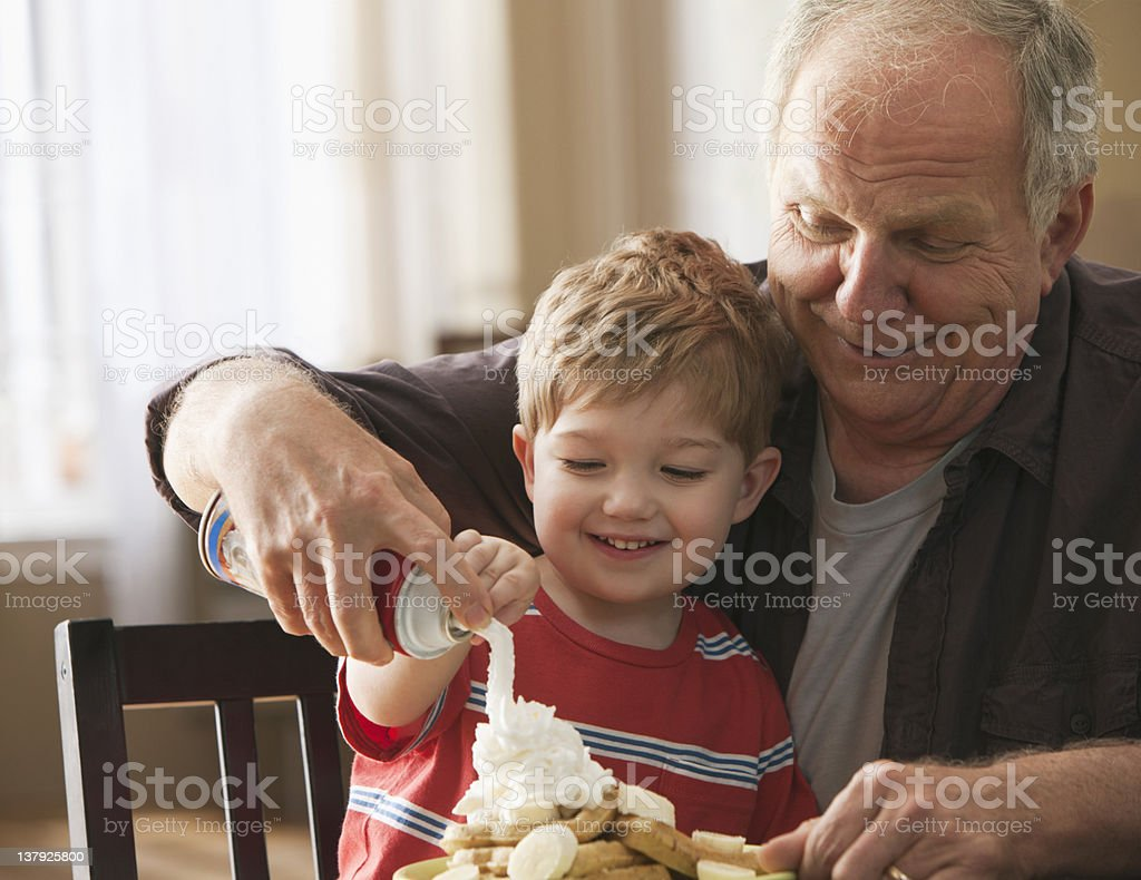 Grandfather and grandson using whipped cream on waffles stock photo
